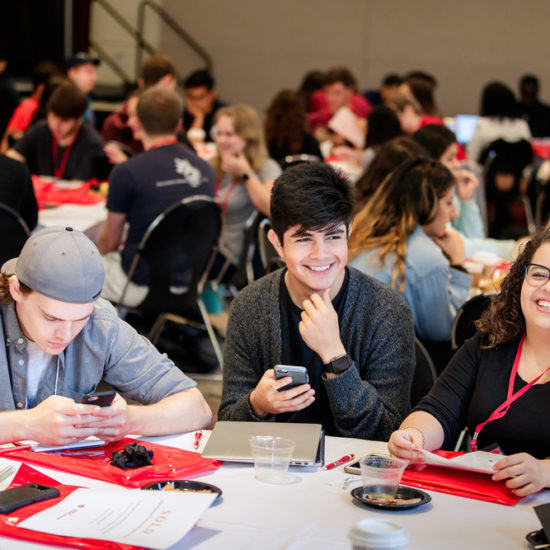 Students sitting at table, smiling
